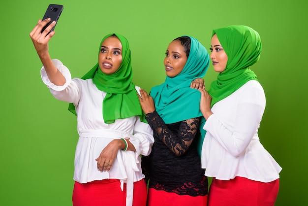 Jovem muçulmana africana contra chroma key com parede verde