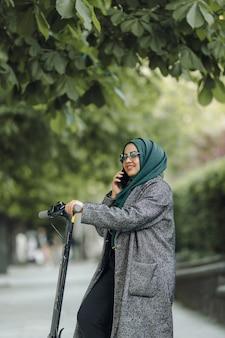 Jovem muçulmana andando de scooter em uma rua