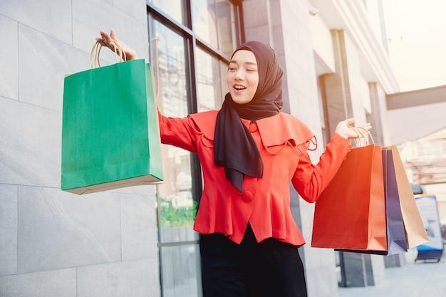 Jovem muçulmana árabe com roupas de hijab de véu, segurando sacolas de compras e andando pelas ruas da cidade. hora das compras. arranha-céus modernos em segundo plano.