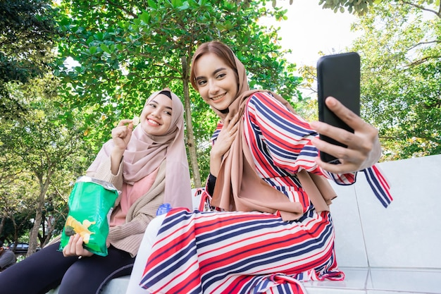 Jovem muçulmana asiática com lenço na cabeça encontrar amigos e usar o telefone no parque para tirar uma selfie juntos