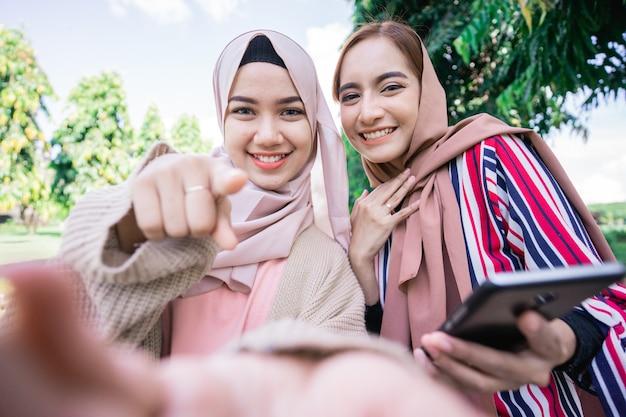 Jovem muçulmana asiática com lenço na cabeça encontrar amigos e usar o telefone no parque