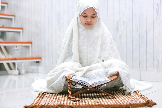 Jovem muçulmana asiática lendo o livro sagrado alquran no tapete de oração em casa