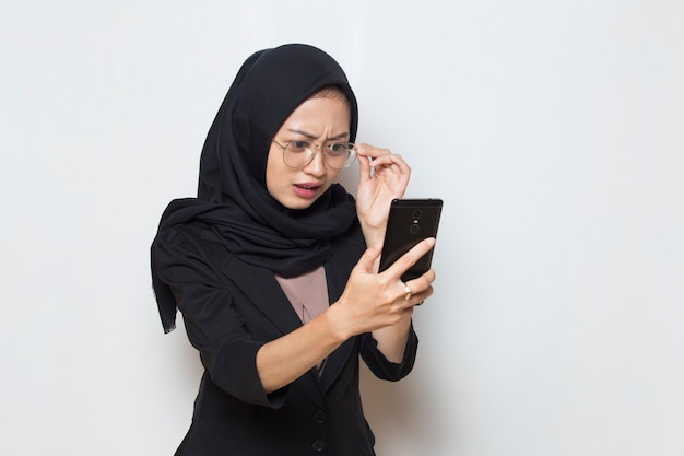 Jovem muçulmana asiática surpresa com óculos usando telefone celular em fundo branco