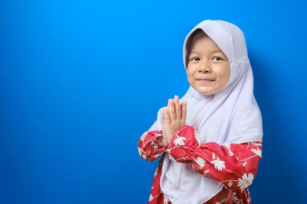 Jovem muçulmana asiática usando gesto de hijab para saudar e dar as boas-vindas ao convidado do eid mubarak