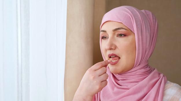 Jovem muçulmana bebe vitamina com água.