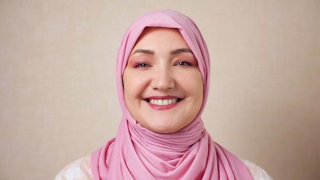 Jovem muçulmana com lenço na cabeça rosa sorrindo, olhando para a câmera