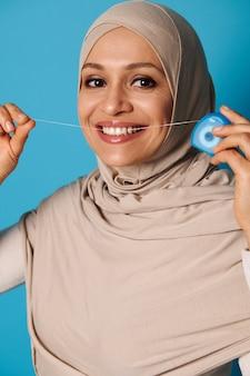 Jovem muçulmana com um sorriso lindo e saudável passando fio dental nos dentes