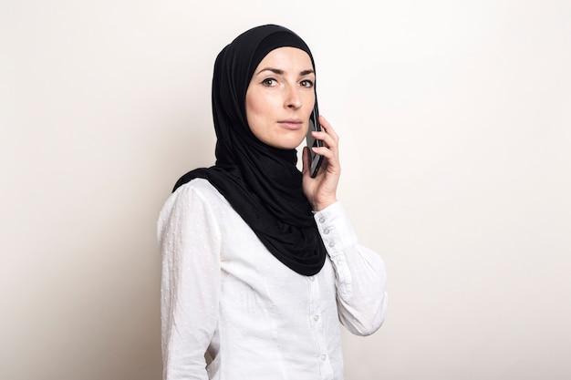 Jovem muçulmana em hijab falando ao telefone e olhando para a câmera