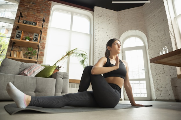 Jovem muçulmana esportiva fazendo aulas de ioga em casa