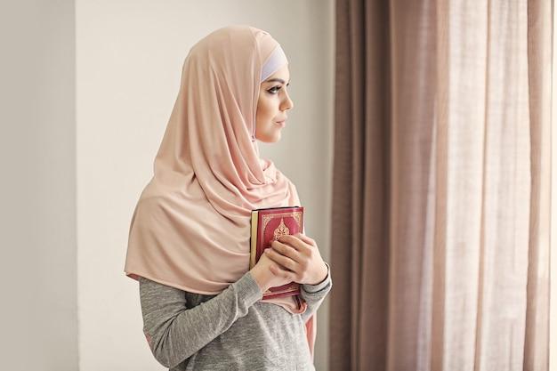 Jovem muçulmana segurando o alcorão e orando dentro de casa