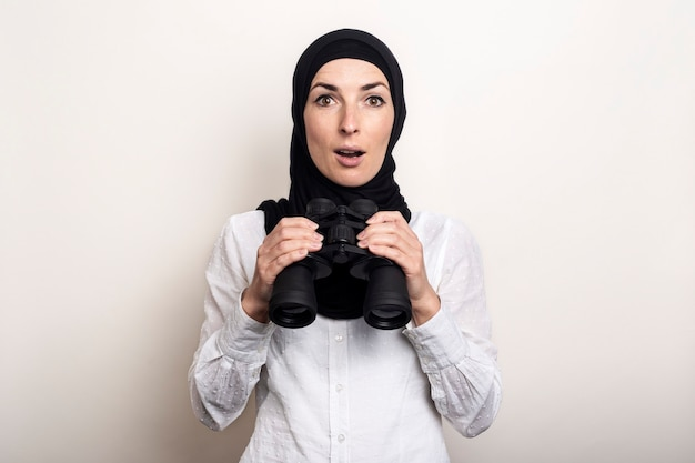 Jovem muçulmana surpresa e amigável com camisa branca e hijab segurando binóculos