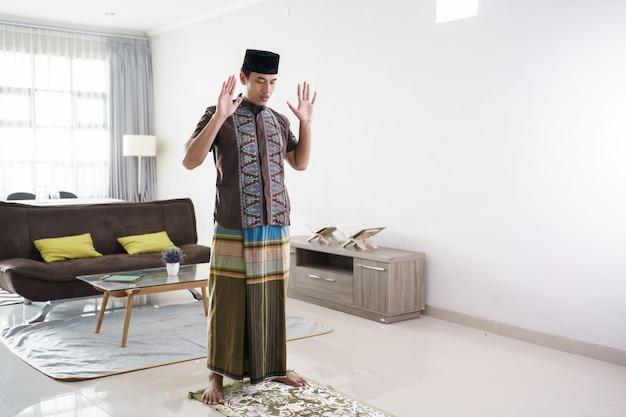 Jovem muçulmano asiático rezando em casa takbir antes de iniciar a oração