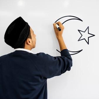 Jovem muçulmano escrevendo em um quadro branco