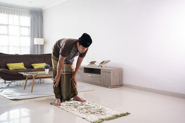 Jovem muçulmano rezando em casa gesto de rukuk