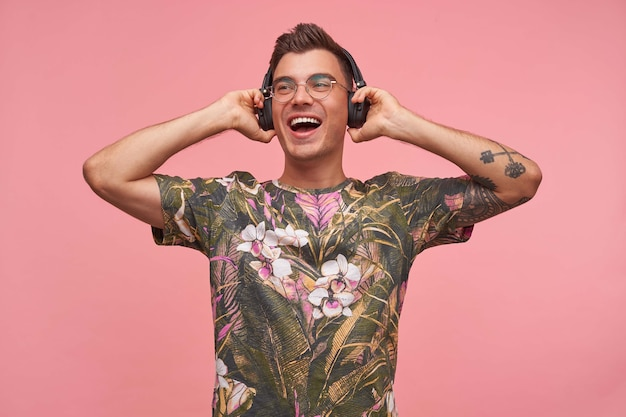 Jovem muito alegre segurando fones de ouvido e ouvindo música, estando de bom humor, usando óculos e camiseta florida, isolado