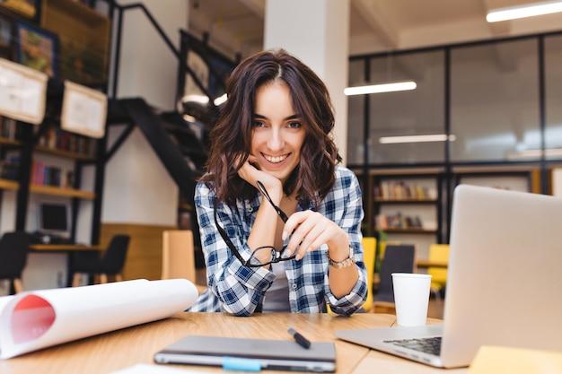 Jovem muito alegre sentada na mesa ao redor do material de trabalho. sorrir, projetar, trabalhar como freelancer, vida de estudante, bom humor, carreira, grande sucesso.