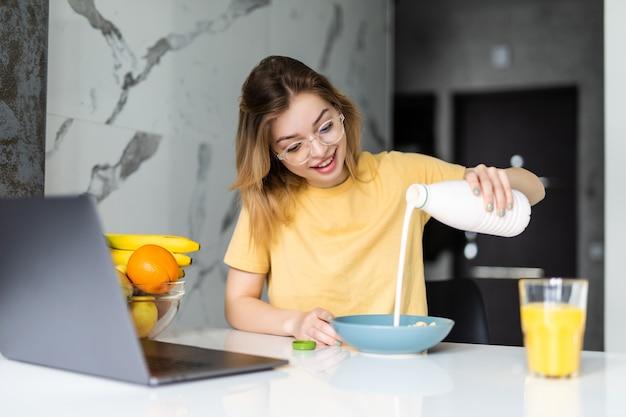 Jovem muito alegre tomando café da manhã enquanto está sentado à mesa da cozinha, trabalhando no laptop