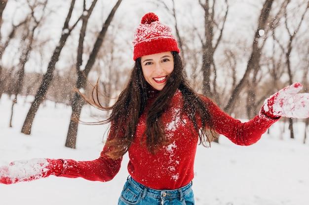 Jovem muito animada, cândida, sorridente, feliz, usando luvas vermelhas e chapéu, suéter de malha, andando brincando no parque na neve, roupas quentes, se divertindo