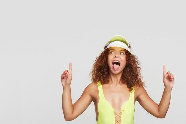 Jovem muito animada com cabelos ruivos e penteado casual, sacudindo a língua enquanto aponta para cima com o dedo indicador, isolado sobre o fundo branco