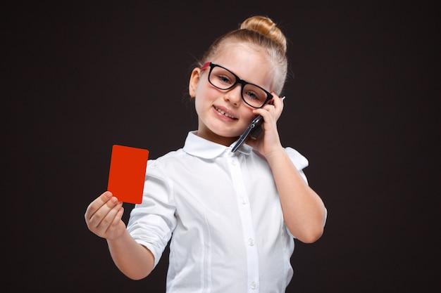 Jovem muito bonita camisa branca e calça preta segurar o cartão vermelho e falar ao telefone