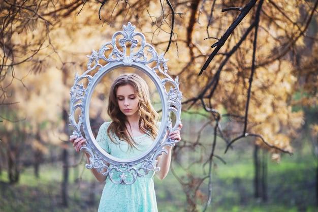 Jovem muito bonita com a moldura do espelho. aparência de boneca. mulher com cabelo castanho em um vestido turquesa na natureza. cabelo longo. luz natural. modelo posando na natureza.