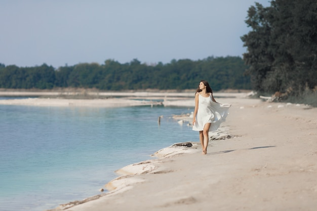 Jovem muito bonita com cabelos longos em um vestido branco à beira do lago. a garota está gostando do resto.