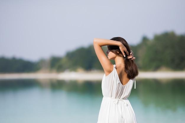 Jovem muito bonita com cabelos longos em um vestido branco à beira do lago. t