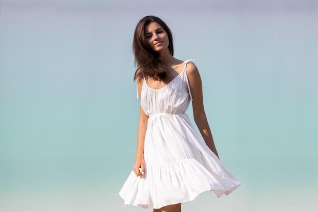 Jovem muito bonita com cabelos longos em um vestido branco à beira do lago.