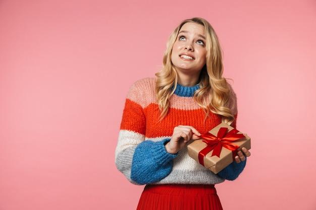 Jovem muito bonita posando isolada sobre uma parede rosa segurando uma caixa de presente