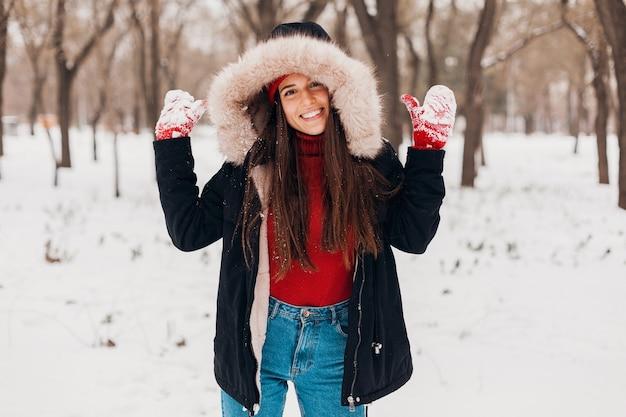 Jovem, muito cândida, sorridente, feliz, com luvas vermelhas e chapéu, casaco preto, andando brincando no parque na neve com roupas quentes, se divertindo