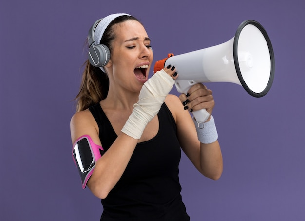 Jovem, muito desportiva, usando pulseira de fita, fones de ouvido e uma braçadeira de telefone com pulso ferido enrolado em bandagem falando por alto-falante isolado na parede roxa