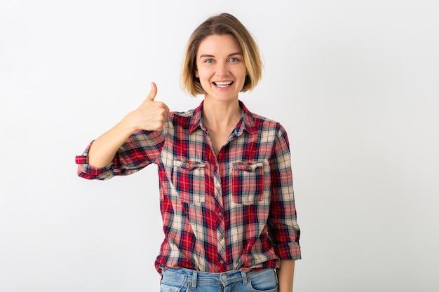 Jovem muito engraçada e emocional em camisa quadriculada posando isolada na parede branca do estúdio, mostrando o polegar para cima gesto