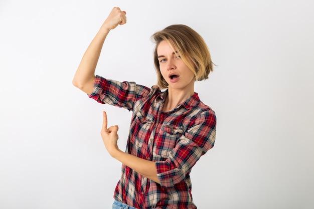 Jovem muito engraçada e emocional em camisa quadriculada posando isolada na parede branca do estúdio, mostrando um gesto de força