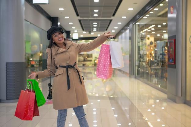 Jovem muito feliz com várias sacolas de compras no shopping