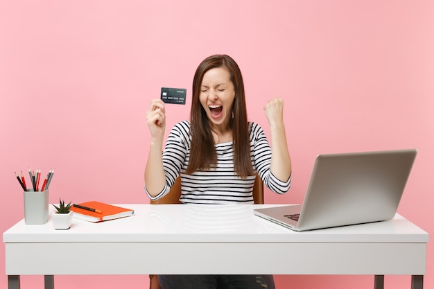 Jovem muito feliz segurando um cartão de crédito fazendo um gesto de vencedor gritando sim trabalhando, sente-se no escritório com o laptop