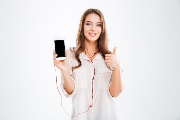 Jovem muito fofa com fones de ouvido, ouvindo música com o smartphone e mostrando o gesto de polegar para cima isolado em uma parede branca
