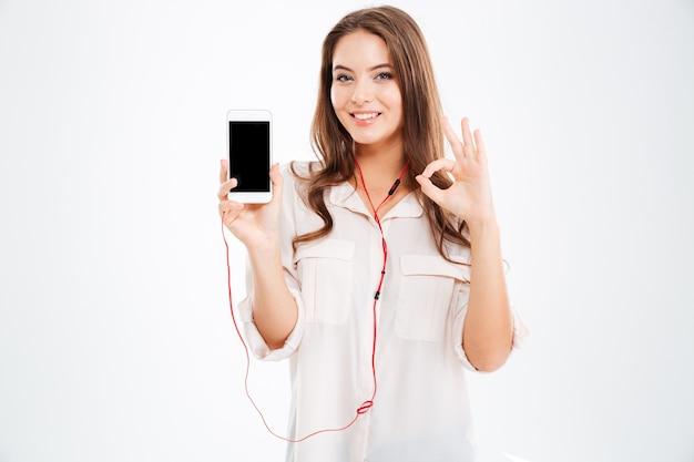 Jovem muito fofa com fones de ouvido, ouvindo música com smartphone e mostrando um gesto de ok isolado em uma parede branca