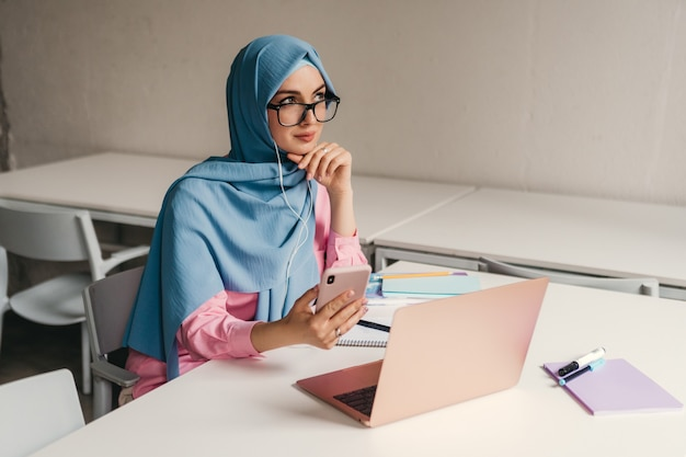 Jovem, muito moderna, mulher muçulmana em hijab trabalhando em um laptop na sala de escritório, educação online