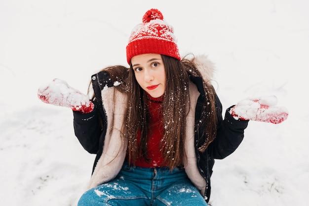 Jovem muito perplexa com luvas vermelhas e chapéu de malha, vestindo um casaco de inverno, sentada na neve no parque, roupas quentes
