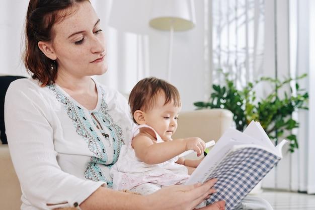 Jovem muito séria sentada no sofá em casa com a filha no colo e lendo um livro de negócios