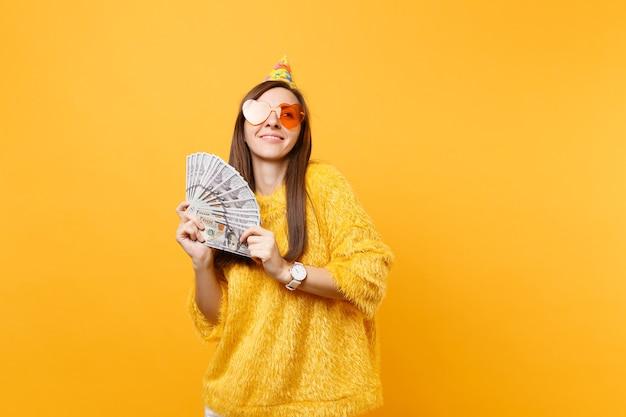 Jovem muito sonhadora com chapéu de festa de aniversário de óculos coração laranja olhando para cima segurando o pacote de lotes de dólares em dinheiro comemorando isolado em fundo amarelo. pessoas sinceras emoções, estilo de vida.