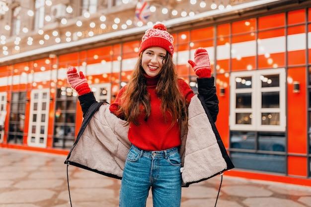Jovem, muito sorridente, animada, mulher feliz com luvas vermelhas e chapéu de malha, vestindo um casaco de inverno, andando na cidade, rua de natal, roupas quentes estilo
