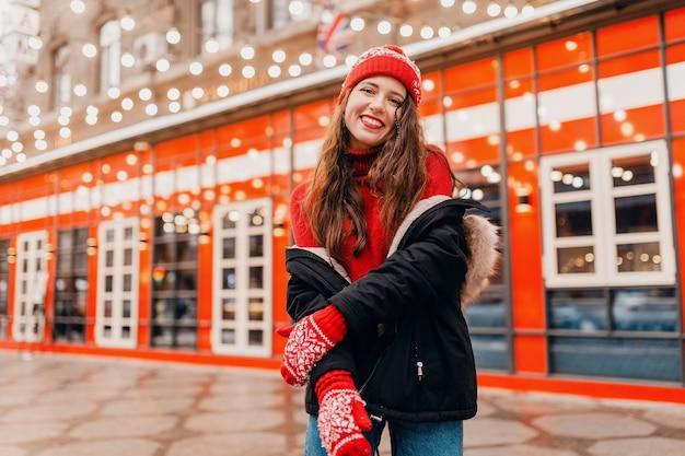 Jovem, muito sorridente, feliz, com luvas vermelhas e chapéu de malha, vestindo um casaco de inverno, andando na cidade, natal, rua, roupas quentes estilo tendência da moda