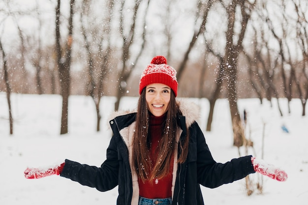 Jovem, muito sorridente, feliz, com luvas vermelhas e chapéu de malha, vestindo um casaco de inverno, caminhando no parque em um dia de neve, roupas quentes