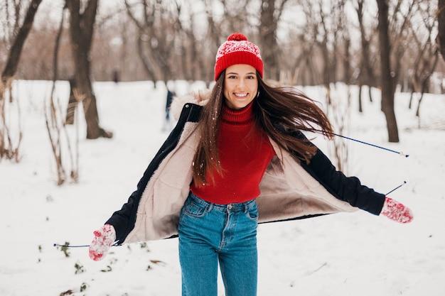 Jovem, muito sorridente, feliz, com luvas vermelhas e chapéu de malha, vestindo um casaco de inverno, caminhando no parque na neve, roupas quentes