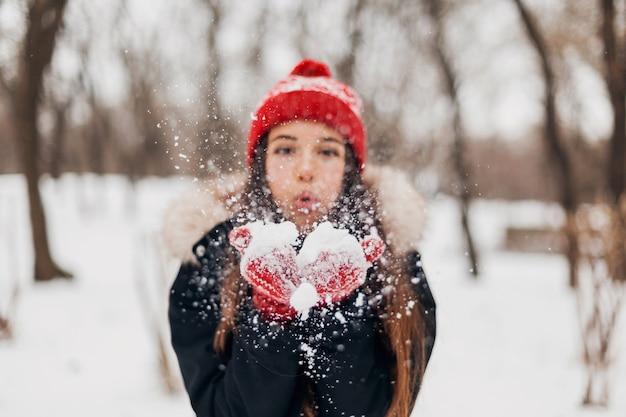 Jovem, muito sorridente, feliz, com luvas vermelhas e chapéu de malha, vestindo um casaco de inverno, caminhando no parque, soprando neve