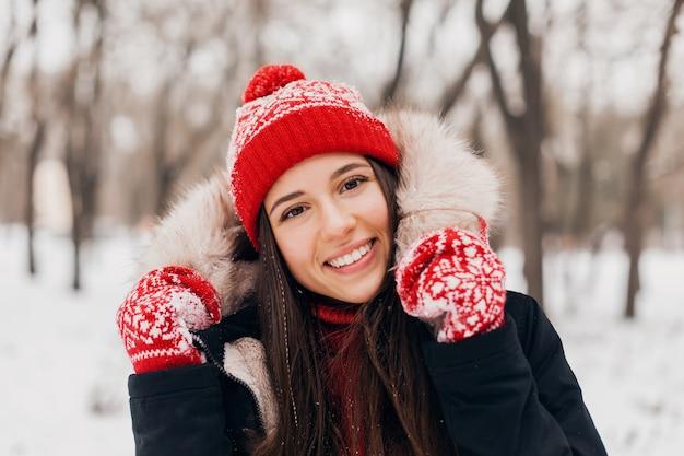Jovem, muito sorridente, feliz, com luvas vermelhas e chapéu de malha, vestindo um casaco de inverno com capuz de pele, andando no parque na neve, roupas quentes