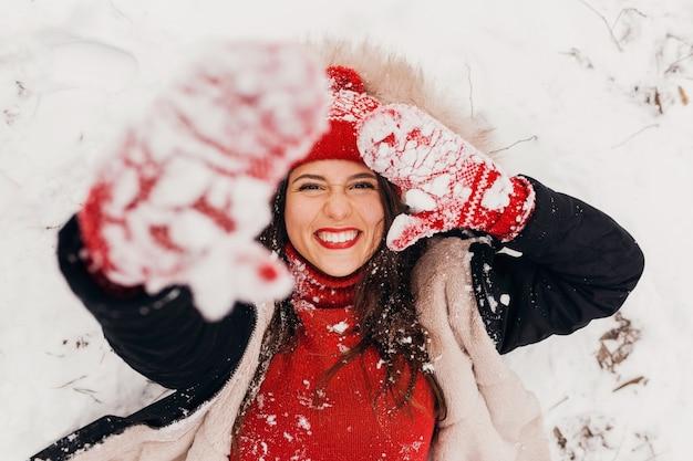 Jovem, muito sorridente, feliz, com luvas vermelhas e chapéu de malha, vestindo um casaco de inverno, deitado no parque na neve, roupas quentes, vista de cima