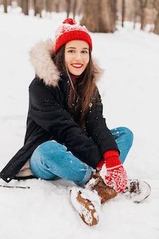 Jovem, muito sorridente, feliz, com luvas vermelhas e chapéu de malha, vestindo um casaco de inverno, sentado na neve no parque, roupas quentes