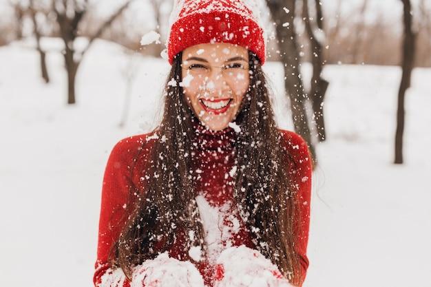 Jovem, muito sorridente, feliz, com luvas vermelhas e chapéu, suéter de malha, caminhando no parque na neve, roupas quentes, se divertindo